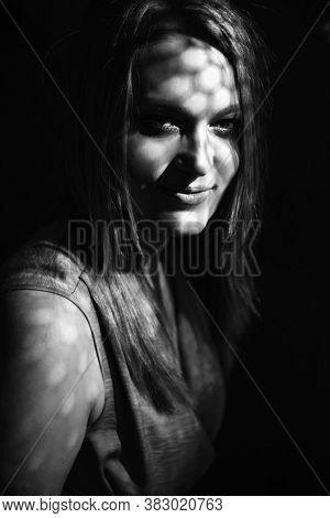 Beautiful mid adult woman with interesting pattern of light and shadow on her face. Beauty female black and white portrait.