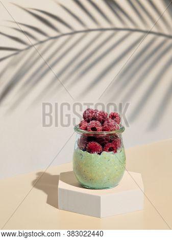 Green Matcha Overnight Oats Dressed Frozen Raspberries. Glass Jar With Breakfast Oats On Hexagon Ped