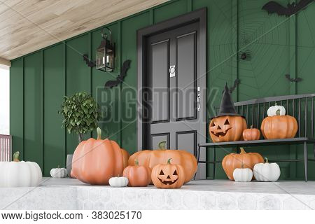 Carved Pumpkins, Bats And Spiders On Floor And Bench Near Modern House With Black Front Door, Tree I