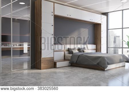 Corner Of Stylish Bedroom With White And Gray Walls, Concrete Floor, Comfortable King Size Bed And H