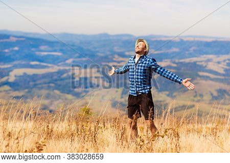 Carefree Man On Top Of Mountains Enjoying Freedom With Arms Outstretched. Young Tourist Man Breathin