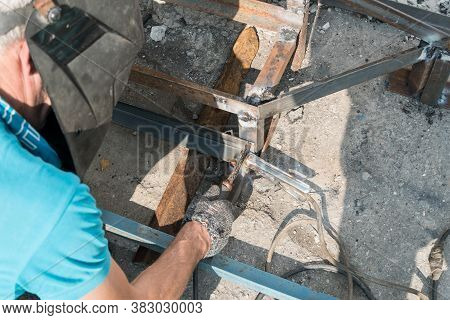 A Working Welder Builds Or Repairs A New Porch And Facade Of A Building Or Structure. Construction A