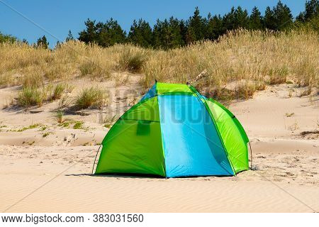 Wind Breaker Tent On A Sandy Beach By The Sea. Nobody. Colorful Tent Protection From Wind And Sunbur