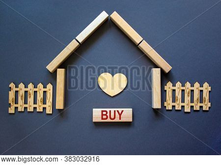 Model Of A Wooden House From Wooden Blocks. Word 'buy'. Wooden Heart And Fence. Copy Space. Business