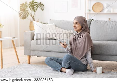 Home Relax. Smiling Muslim Girl In Hijab Unwinding With Smartphone And Coffee On Floor In Living Roo
