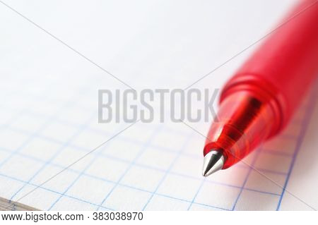 Light Background On A School Theme With Place For Text. Red Pen And Squared Notebook Sheet Close-up.