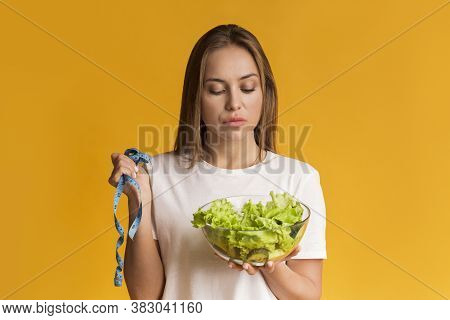 Weightloss And Dieting Concept. Pensive Young Woman Holding Measuring Tape And Looking At Lettuce Sa