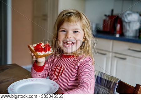 Cute Funny Toddler Girl Eats Sweet Bun For Breakfast. Happy Child Eating Bread Roll With Strawberry