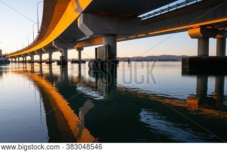 Morning Sun Strikes Side Tauranga Harbour Bridge In Golden Hue Reflected Leading Converging Lines In