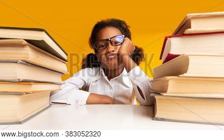 Boring Lesson. Discontented Black Schoolgirl Sitting At Books Over Yellow Background. Studio Shot