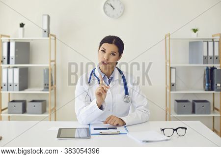 Doctor Online. Hispanic Female Doctor Looking At The Camera Says Diagnose While Sitting At A Table I