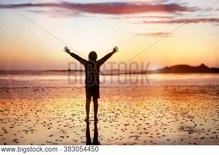 Silhouette of a boy on a beach with hands raised in the sunset over the sea concept for religion, worship, prayer and praise