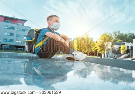 Boy, schoolboy in protective mask sits near the school in sunny September day