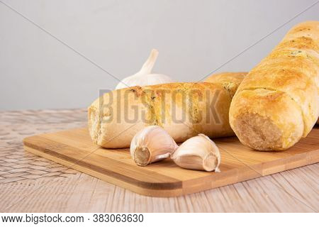 Garlic Bread Stuffed With Cheese Arranged On A Cutting Board With Garlic Around It, On A Table, Sele