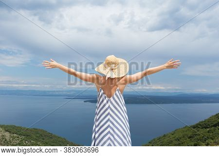 Rear View Of Young Woman Wearing Striped Summer Dress And Straw Hat Standing In Super Bloom Of Wildf