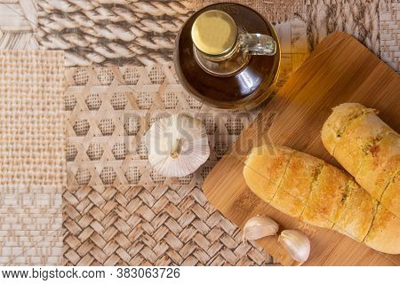 Garlic Bread Stuffed With Cheese Arranged On A Cutting Board With Garlic Around It And A Bottle Of O