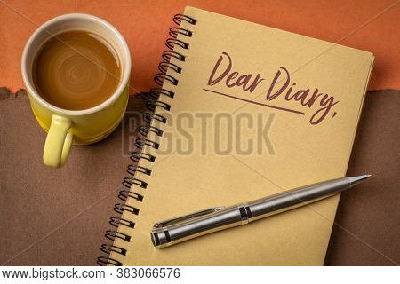 Dear Diary - handwriting in a spiral sketchbbok with a cup of coffee, jouranling concept