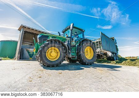 Bavaria / Germany - August 20, 2020: John Deere Tractor With A Loader Wagon, Working On A Biogas Pla