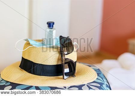 Travel Set With A Hat On A Bag With A Mask, Hand Sanitiser And Sunglasses. Travel Safety Concept.