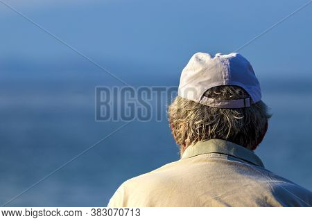 Close Up Shot Of The Back Of A Senior Man's Head With Gray Hair Wearing A Cup Looking The Sea.
