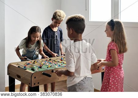 Group Of Multi Cultural Cute Children Stand Indoor Spend Playtime With Friends Playing Foosball Toge