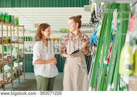 Happy young assistant of gardening shop in apron and shirt showing new models of worktools to mature brunette female customer