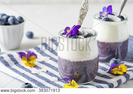 Blueberry Yogurt Parfait With Chia Pudding, Coconut Yoghurt, Fresh Berries And Flowers In Glasses Wi