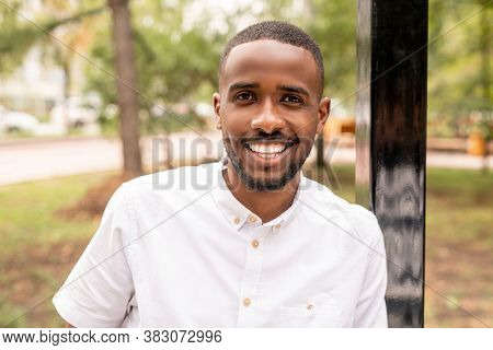Young cheerful man of African ethnicity looking at you with white toothy smile while standing in front of camera in natural environment