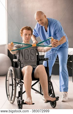 Mature clinician in blue uniform helping young patient in wheelchair while supporting his hand during physical exercise with resistance band