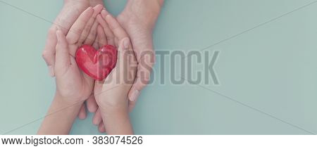 Adult And Child Hands Holding Red Heart, Organ Donation, Wellbeing, Family Health Insurance And Csr