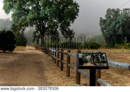 Hiking Trail Head  Leads Past Photo Podium Showing Similar Scene Of Wooden Fence  Heading Into The F