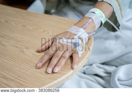 Patient Woman With Receiving Intravenous Fluid Directly Into A Vein While Her Resting On Hospital Be