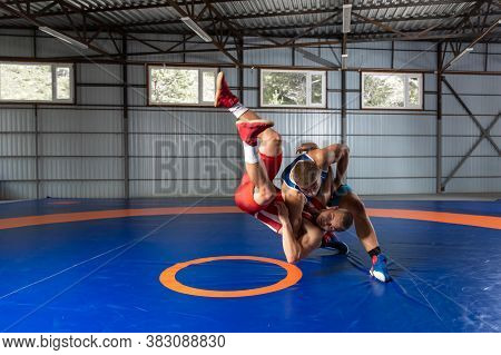 The Concept Of Fair Wrestling. Two Greco-roman  Wrestlers In Red And Blue Uniform Wrestling   On A W