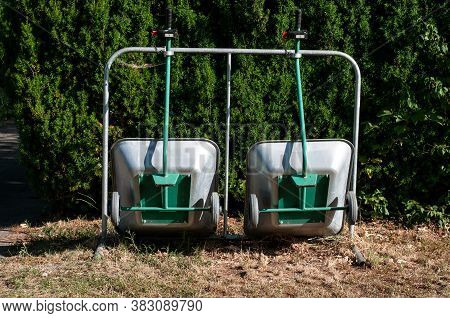 Close-up Of Metal Barrows Fixed Upright Next To A Yew Hedge In A Cemetery