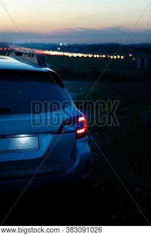 Car Taillights At Night Time. City Lights On Background