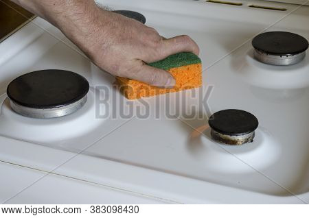 Man Is Cleaning The Stove With Kitchen Sponge. Male Hand With An Orange Kitchen Sponge. Middle-aged