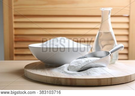 Baking Soda In Scoop And Bowl On Wooden Table