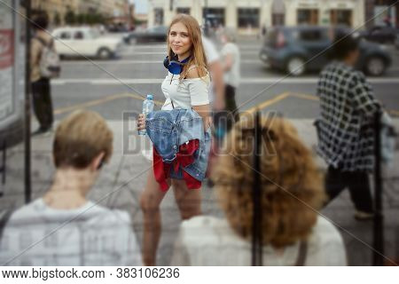 Young Woman Walks In Crowd. Caucasian Attractive Slim Female About 25 Years Old In Casual Cloth Is W