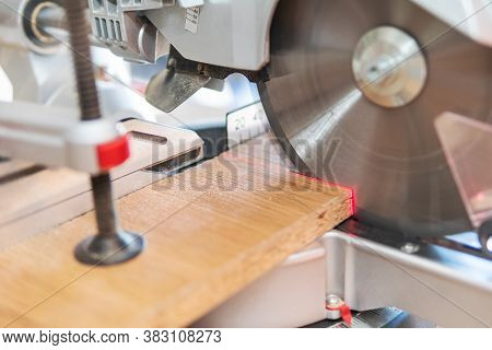 Circular Saw Cuts The Board At The Laser-marked Level. The Board Is Clamped In A Locksmith Clamp.