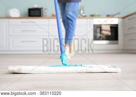 Young Woman Mopping Floor In A Kitchen