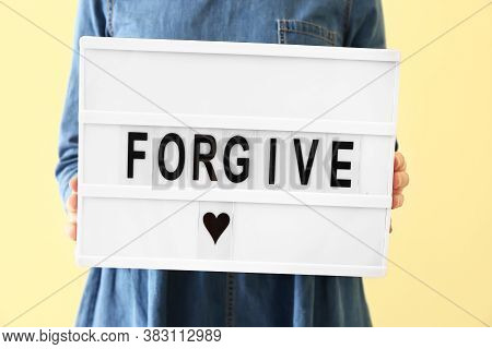 Woman Holding Board With Word Forgive On Color Background, Closeup