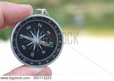Classic Navigation Compass In Hand In Summer Against Background Of Sandy Beach As Symbol Of Tourism