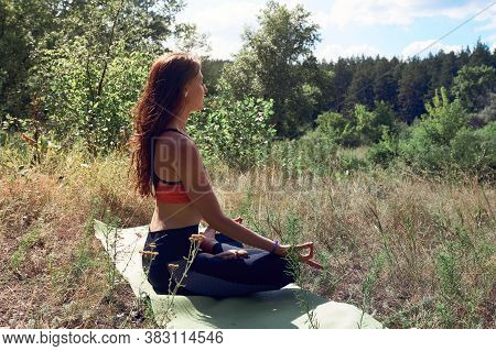 Beautiful Young Woman In Sportive Top And Leggings Meditating In The Morning On The Nature. Healthy