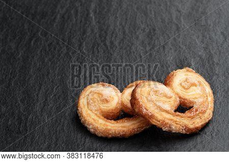 Flaky  Pastry Hearts Glazed With Caramelized Sugar On Black Stone Background