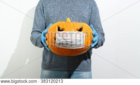 New Normal Concept. An Unrecognizable Man In Rubber Gloves Holds In Front Of Him A Carved Halloween