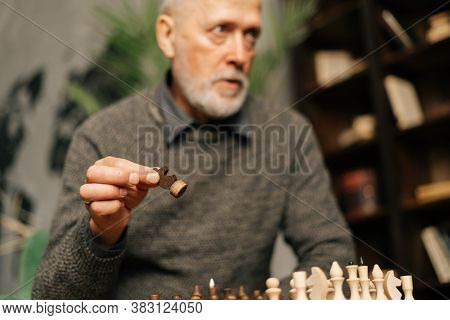 Caucasian Mature Adult Bearded Gray-haired Man Making Move At Chess Game, Sitting At Home On Backgro