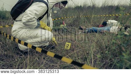 Woman With Bacteriological Protection Equipment Examining Evidence Next To A Corpse Outdoors