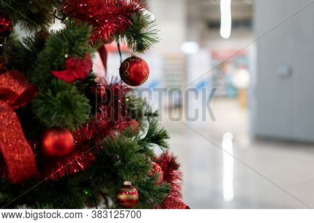 Close Christmas Tree In A Shopping Center Against The Background Of Blurry Shop Windows. Free Space