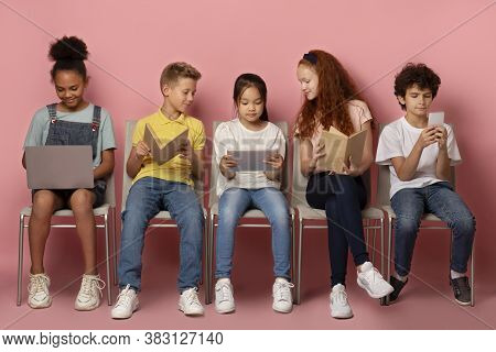 Elearning Concept. Diverse Schoolchildren Using Tablet, Laptop, Smartphone And Books To Study Online