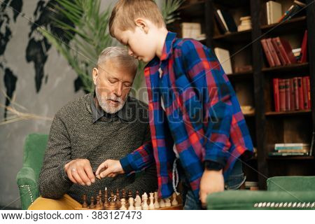 Grandfather And Grandson Setting Wooden Chess Figures On Chessboard Preparing To Play Sitting At Des
